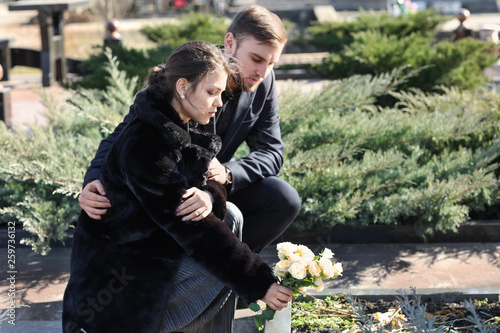 Fotografía  Couple putting flowers on grave of their relative at funeral