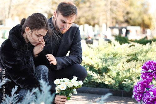 Fotomural Couple putting flowers on grave of their relative at funeral