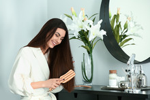 Beautiful Young Woman Brushing Her Healthy Long Hair At Home