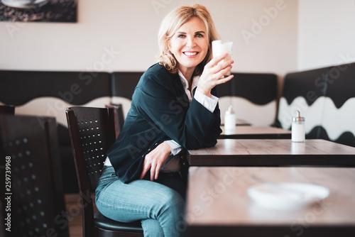 Fotografie, Obraz  Attraktive,  ältere Frau sitzt im Cafe, hält einen Latte Macchiato in der Hand u