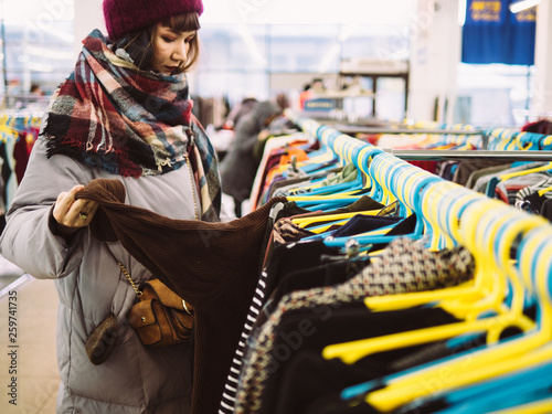 Fotomural  Young woman is browsing a rail of clothes at mall store