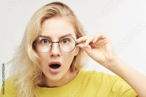 Fotografija  Surprised woman in round glasses with open mouth and bulging eyes looks into cam