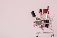 Creative Concept With Shopping Trolley With Makeup On A Pink Background. Perfume, Sponge, Brush, Mascara, Pencil, Nail File, Eye Shadow, Lip Gloss In The Basket, Copy Space