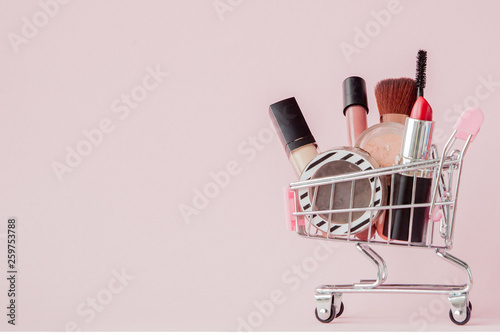 Fotografia Creative concept with shopping trolley with makeup on a pink background