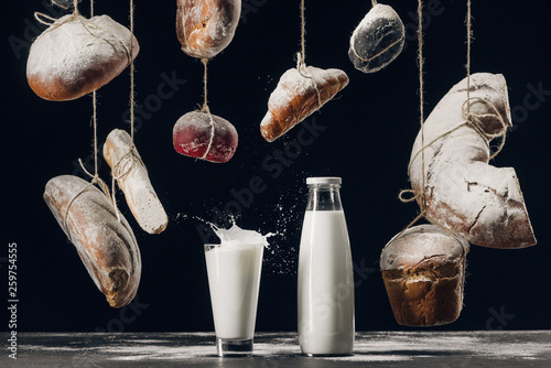 milk splashing in glass on table and bread with flour hanging on strings isolated on black