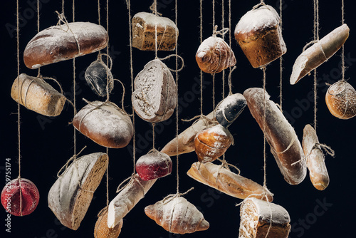white and brown bread and pastry hanging on ropes isolated on black