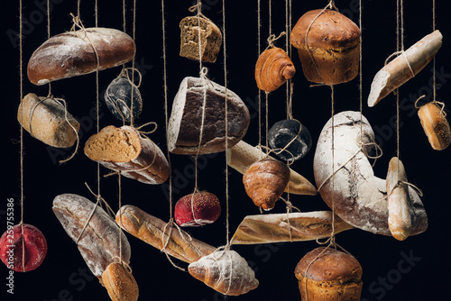 loaves of white and brown bread and pastry hanging on ropes isolated on black
