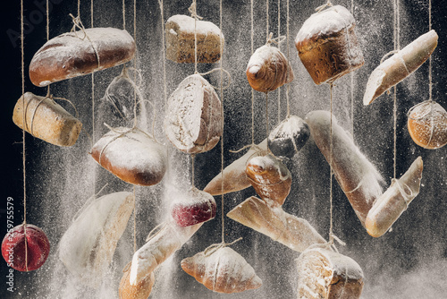 flour falling at fresh homemade bread hanging on ropes