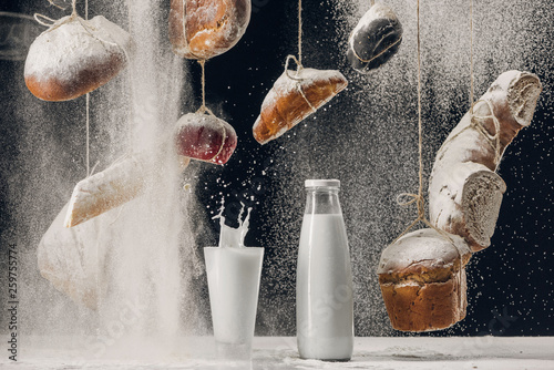 milk splashing in glass on table and four falling on bread hanging on strings isolated on black