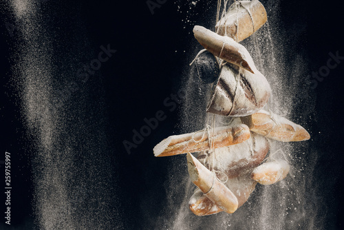 white flour falling at bread, baguettes and croissant on ropes on black background