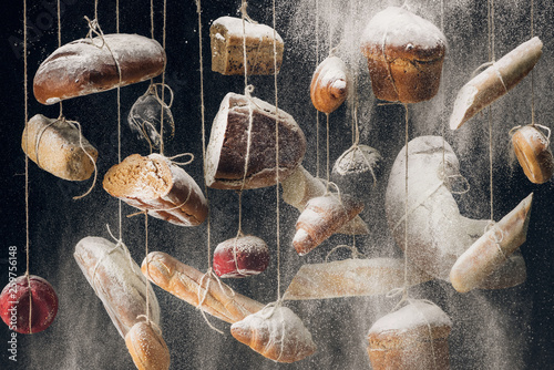 flour falling at white and brown bread and pastry hanging on ropes