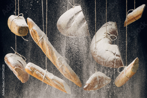 white flour falling at fresh baked bread, baguettes and croissant hanging on ropes on black background