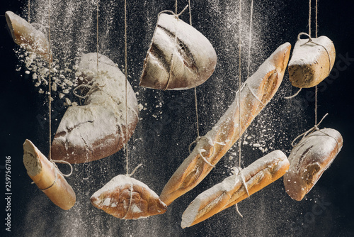 flour falling at fresh baked bread hanging on ropes on black background
