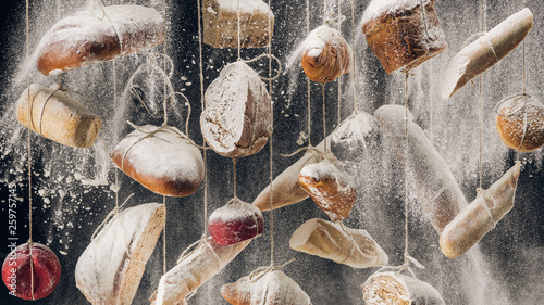 flour falling among fresh homemade bread and pastry hanging on ropes
