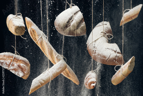 white flour falling at baked bread, baguettes and croissant hanging on ropes on black background