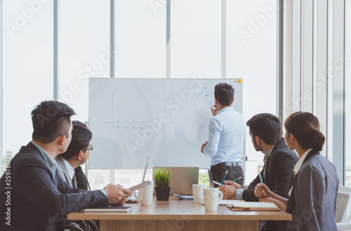 Obraz Businessman leader writing on the whiteboard present business marketing graph while meeting with colleagues in office.Business Team Meeting Presentation,Conference Planning Business Concept - fototapety do salonu