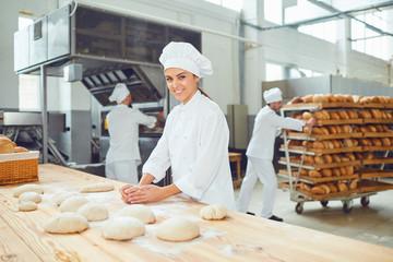 Pekarica se smiješi s kolegama u pekari.