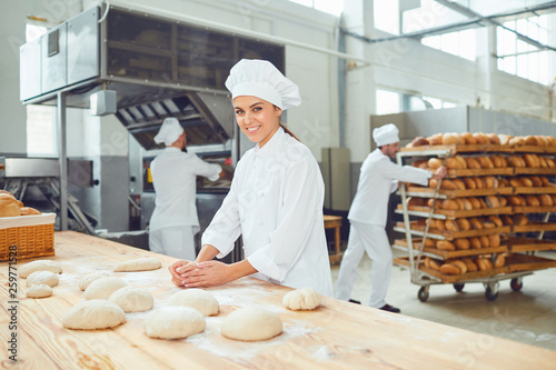 Foto op Canvas Bakkerij A woman baker smileswith colleagues at a bakery.