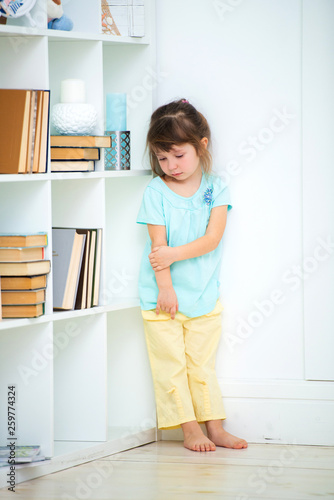 Canvas Print A sad little delinquent girl stands punished in the corner