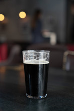 Pint Of Dark Ale On A Wooden Table