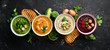 Leinwandbild Motiv Assortment of colored vegetable cream soups. Dietary food. On a black stone background. Top view. Free copy space.