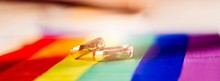 Two Gold Wedding Rings On Rainbow Lgbt Flag. Homosexual Marriage.