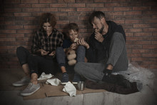 Poor Homeless Family Sitting O...