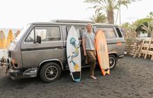 Happy Adult Guy Standing Between Craft Surf Boards And Old Van In Yard