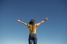 From Below Woman Standing With Hands Apart Against Blue Cloudless Sky