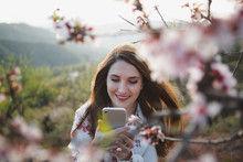 Attractive Cheerful Lady Taking Selfie On Mobile Phone Near Blooming Woods In Garden On Mountain