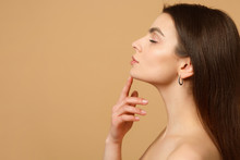 Close Up Brunette Half Naked Woman 20s With Perfect Skin, Nude Make Up Isolated On Beige Pastel Wall Background, Studio Portrait. Skin Care Healthcare Cosmetic Procedures Concept. Mock Up Copy Space.
