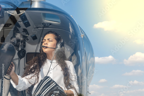 Fotografia  Female pilot in cockpit of helicopter before take off