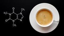 Cup Of Fresh Coffee On A Black Background. Blackboard With The Chemical Formula Of Caffeine. Top View With Copy Space