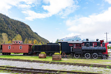 Black Steam Engine/locomotive And Red And Black Snow Plow With Caboose In Public Space On Skagway, Alaska