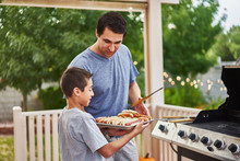 Father And Son Grilling Hot Do...