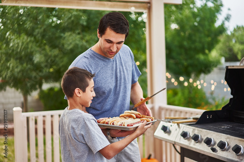 Fototapeta father and son grilling hot dogs together on backyard gas grill obraz