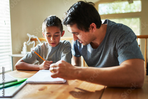 Papel de parede father helping son with homework on table at home