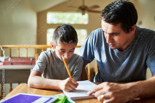 father helping son with homework on table at home Wallpaper Mural