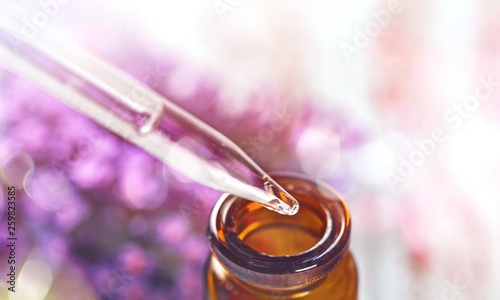 Pile of lavender flowers and a dropper bottle with lavender essence - 259823585