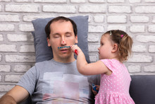 Girl Painting Father's Face With Color Tube
