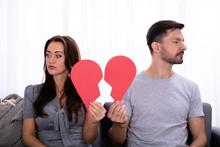 Couple Sitting On Sofa Holding Broken Heart
