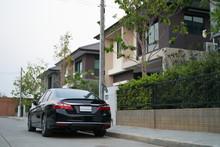 Black Modern Car Parked On Road Of Village House