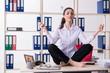 Leinwanddruck Bild Young female employee doing exercises in the office
