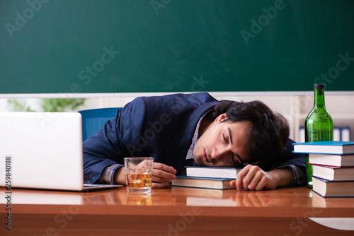 Fotografija  Male teacher drinking in the classroom