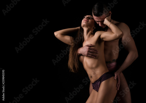 Valokuvatapetti muscular naked man and sexy woman hugging on a dark background, sexual foreplay of a young couple