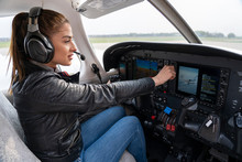 Portrait Of Attractive Young Woman Pilot With Headset In The Cockpit