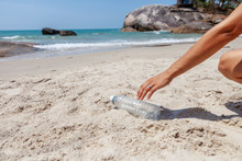 Hand Woman Picking Up Plastic Bottle Cleaning On The Beach , Volunteer Concept. Ecology And Earth Day Concept