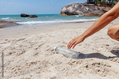 Fotografia Hand woman picking up plastic bottle cleaning on the beach , volunteer concept