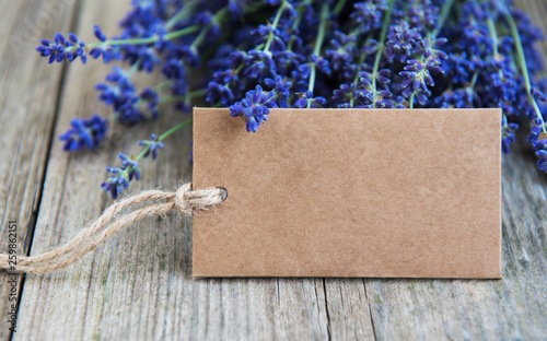 Photo  Empty tag and lavender flowers on a old wooden table