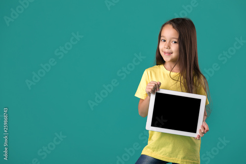 Carta da parati cute little child girl holding tablet with blank screen isolated on blue backgro